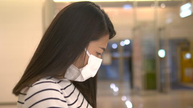 vídeos de stock, filmes e b-roll de jovem asiática com máscara cirúrgica usando telefone inteligente e sentado à distância para prevenir covid-19 - smart