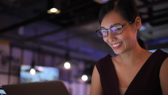 若いアジアの女性がコンピュータを働き、ラップトップモニターを見て - 雇用と労働点の映像素材/bロール