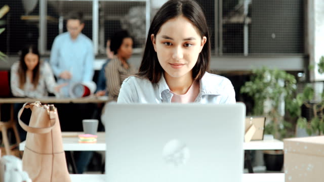 young asian woman working in modern office using laptop - place of work stock videos & royalty-free footage