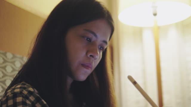 vídeos de stock e filmes b-roll de young asian woman working late using tablet on sofa in bed room at home. - trabalhadora de colarinho branco