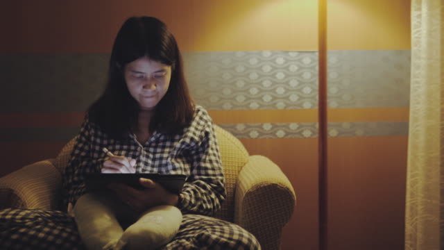 young asian woman working late using tablet on sofa in bed room at home. - digitized pen stock videos & royalty-free footage