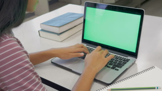 Young Asian woman working on a new project on laptop computer with blank green screen in office, Woman typing keyboard while using internet for online activity