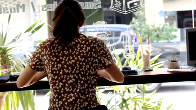 young asian woman working on laptop in cafe - netbook stock videos and b-roll footage