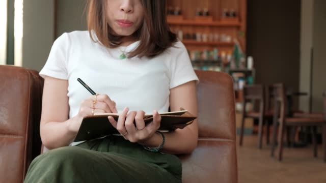 vídeos de stock e filmes b-roll de young asian woman writing journal book in coffee shop. - emprego na comunicação social