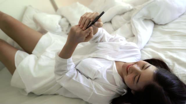 young asian women are using the smart phone on the white bed. technology, internet, communication and people concept. - softness stock videos & royalty-free footage