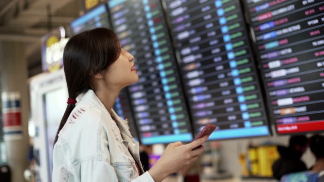Young Asian women checking flight with smart phone at airport for global Journey travel