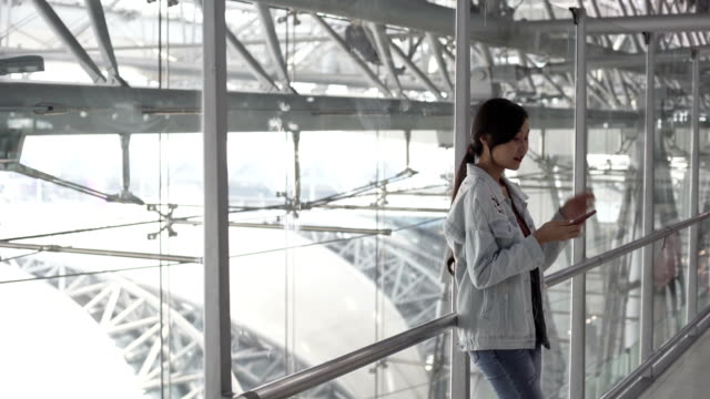 Young Asian women checking flight with smart phone at airport for Journey travel