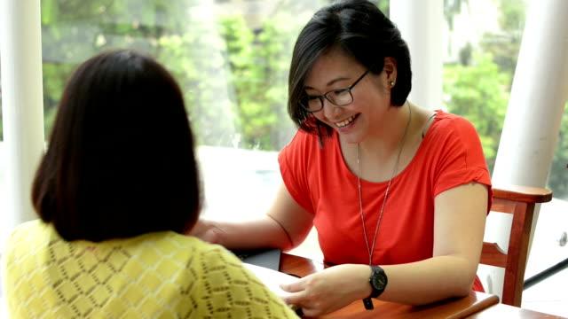 若いアジア女性のディスカッションには、フードコート - note pad点の映像素材/bロール