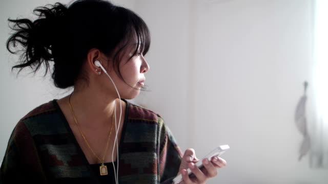 音楽を聴く若いアジア女性