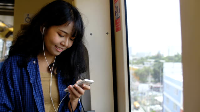 Young asian women listening to music.