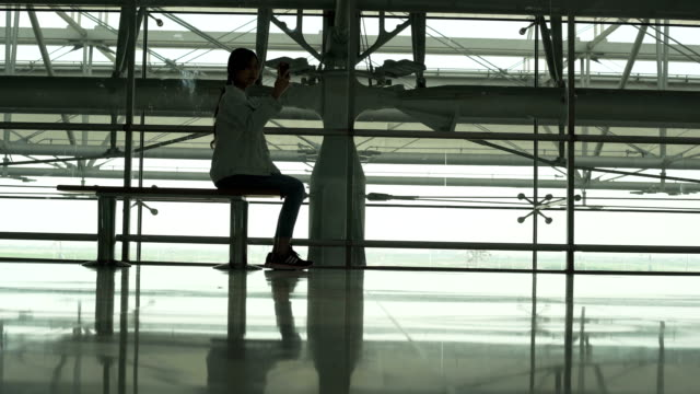 Young Asian women touching with smart phone at airport for Journey travel