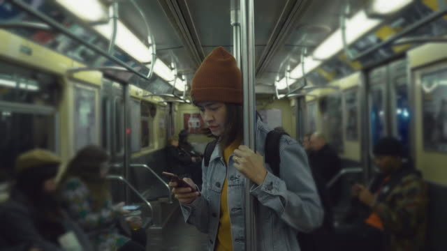 young asian women typing message on the train. - underground train stock videos & royalty-free footage
