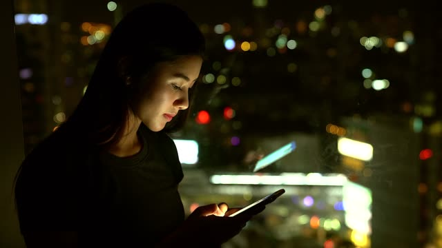 young asian women using mobile at night with the lighting of the city as background. - east asian ethnicity stock videos & royalty-free footage