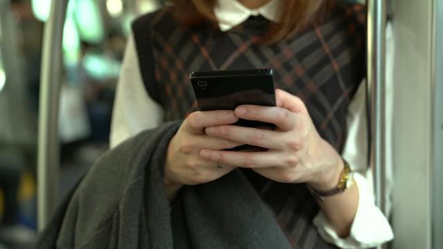 若いアジアの女性は、輸送中に携帯電話を使用して。 - 腕時計点の映像素材/bロール
