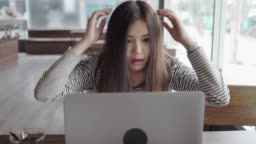 Young asian young woman shock and reacting to loss on laptop at cafe