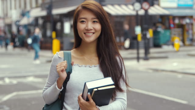 Young Aspiring Chinese Student with books (slow motion)