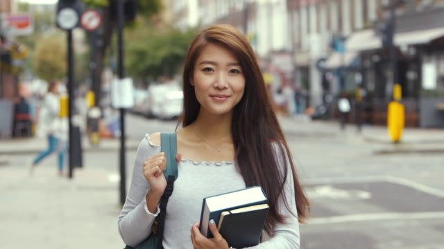 young aspiring chinese student with books (slow motion) - studente universitario video stock e b–roll