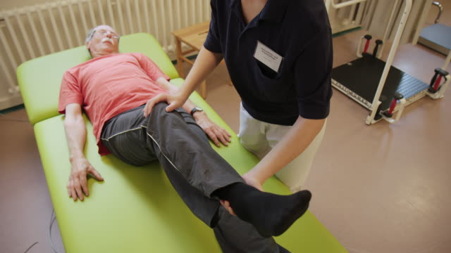young assistant helping senior man in health club - physical therapy stock videos & royalty-free footage
