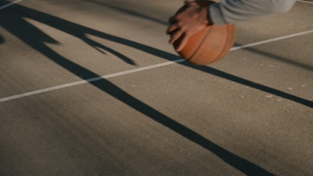 Junge Sportler Ball in Basketballplatz dribbeln