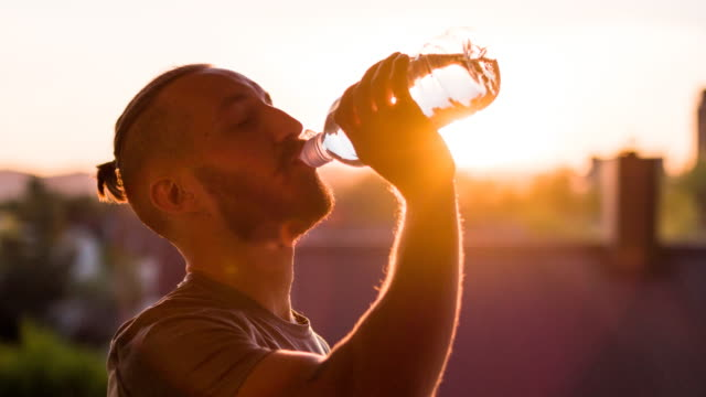 young athlete drinking water at sunset after finishing a run - sweat stock videos & royalty-free footage