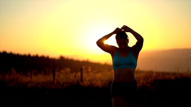 junger sportler fixiert haare nach dem training - joggerin stock-videos und b-roll-filmmaterial