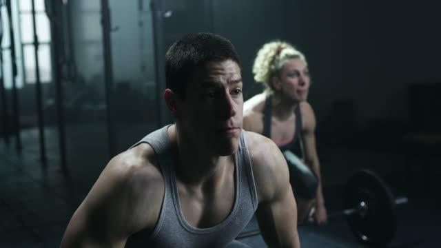 junge sportler mann und frauen, die übung mit gewichten im fitnessstudio - konzentration stock-videos und b-roll-filmmaterial