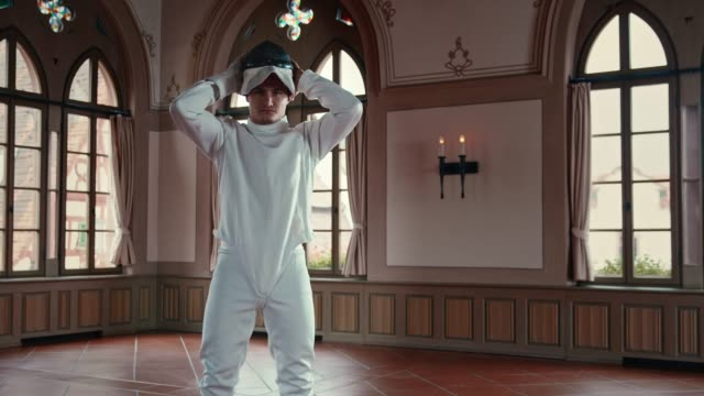 Young athlete wearing fencing mask in castle