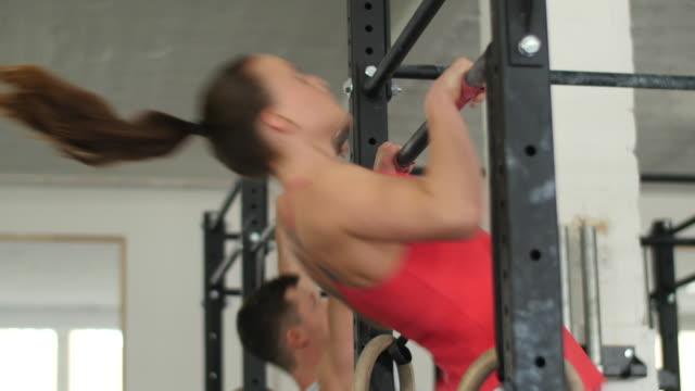 young athlete woman doing pull ups - 後ろで束ねた髪点の映像素材/bロール