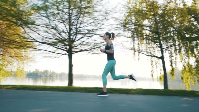 young athlete woman running in park. - morning stock videos & royalty-free footage