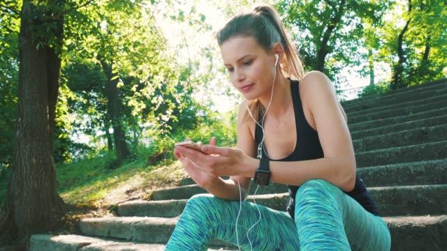 vidéos et rushes de femme jeune athlète à l'aide de téléphone intelligent. - cheveux blonds
