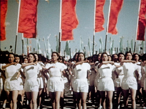 Young athletes march in unison / Madam Sun Yatsen waves at marchers / female athletes in white march toward camera
