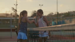 Young athletes walking up to net and shaking hands