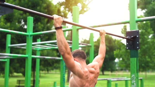 vídeos de stock, filmes e b-roll de jovem atlético fazendo pull-up na barra horizontal - musculação