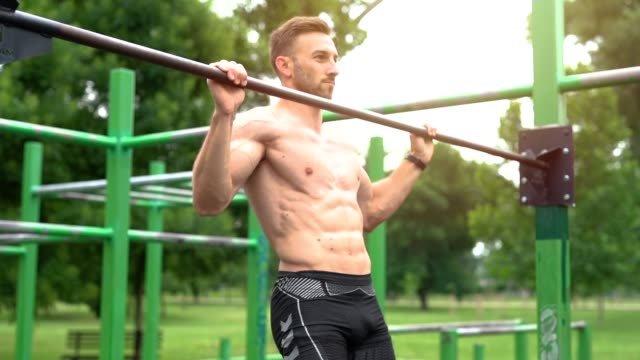 young athletic man doing pull-up on horizontal bar - horizontal bar stock videos & royalty-free footage