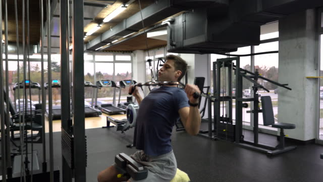 young athletic man exercising on lateral-pull down weight machine in a gym. - lateral pull down weights stock videos & royalty-free footage