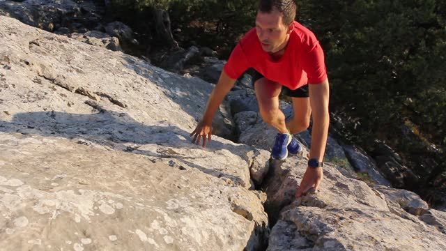young athletic man in shorts and a red t-shirt jogging up a rocky mountain during cardio training for endurance and leg muscle building. sports training - cross country running uphill - smart watch stock videos & royalty-free footage