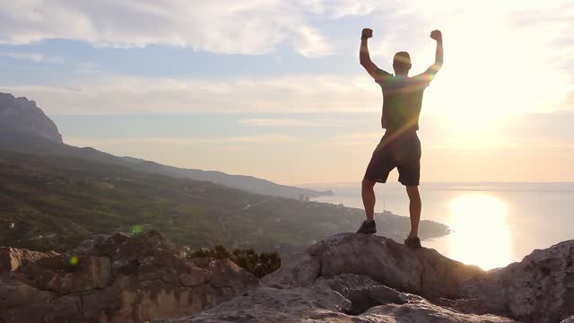 vídeos de stock, filmes e b-roll de a young athletic man in shorts and t-shirt climbs to the top of a cliff and celebrates success with raised hands in the rays of the shining sun in mountains - superar as dificuldades