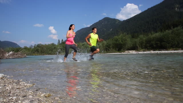 young athletic people running in a river - pedal pushers stock videos & royalty-free footage
