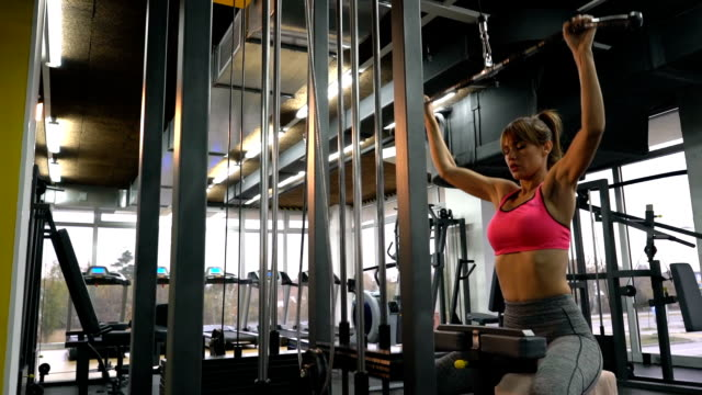 young athletic woman having a sports training on exercise machine in a gym. - lateral pull down weights stock videos & royalty-free footage