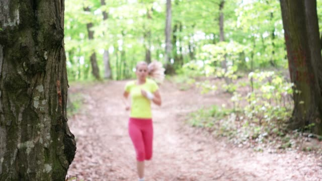 young athletic woman jogging in nature wiping sweat of her forehead. - forehead stock videos and b-roll footage
