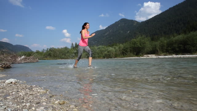 young athletic woman runing in a river - pedal pushers stock videos & royalty-free footage