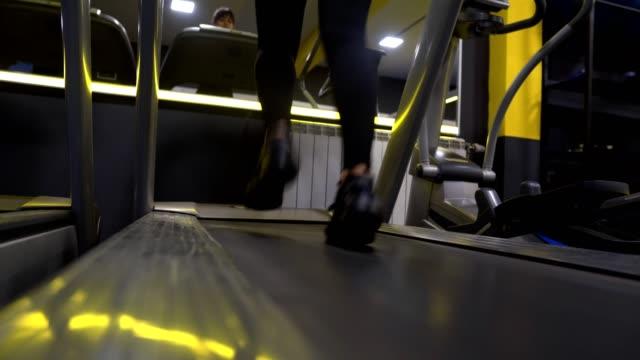 junge athletin läuft auf einer handelsmühle - legging stock-videos und b-roll-filmmaterial