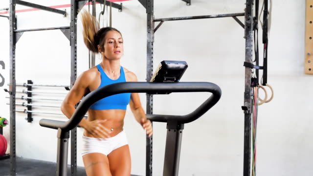 young athletic woman running on a treadmill. - running shorts stock videos & royalty-free footage