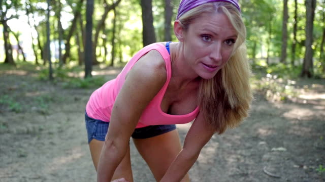 young athletic woman stretching muscles before running in park - running shorts stock videos & royalty-free footage