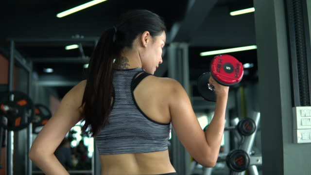 young attractive asian woman working out in the gym using dumbbells - only young women stock videos & royalty-free footage