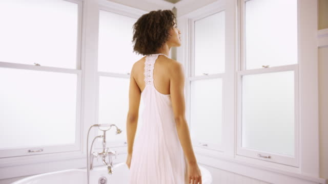 young attractive black woman standing in front of bath tub.  pretty black woman wearing white gown getting ready to take a warm bath. - evening gown stock videos & royalty-free footage