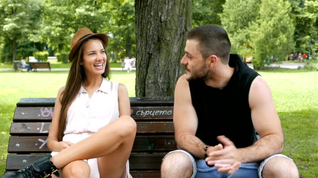 Young attractive boy and girl sitting on a bench in the city park and talking to each other