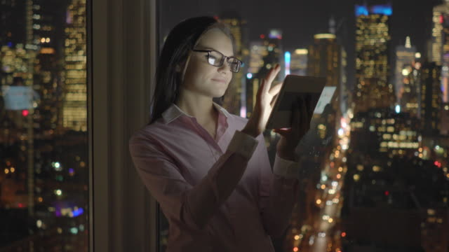 young attractive businesswomen working on computer desk in modern city office at night light. analyzing charts - technophile stock videos & royalty-free footage