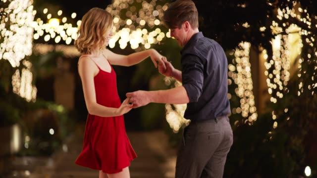 vidéos et rushes de young attractive couple dancing outside building wrapped in lights in evening - robe d'été