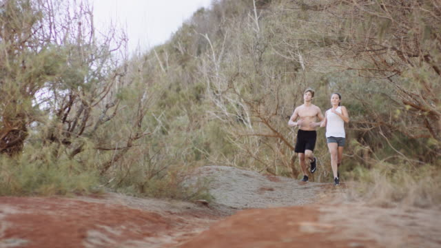 young attractive couple trail running next to the ocean - kauai stock videos and b-roll footage